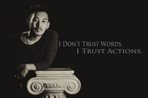 "A man leaning with the words ""I don't trust words, I trust Actions"""